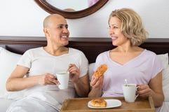 Adultos que presentan con café y pasteles Foto de archivo