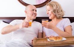 Adultos que presentan con café y pasteles Imagenes de archivo