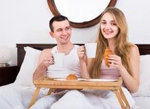 Adultos que presentan con café y pasteles para el desayuno Imagen de archivo libre de regalías