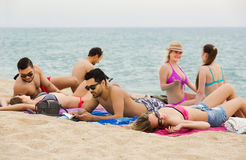 Adultos que se relajan en la playa arenosa Imagen de archivo libre de regalías