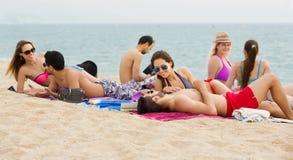 Adultos que se relajan en la playa arenosa Imagenes de archivo