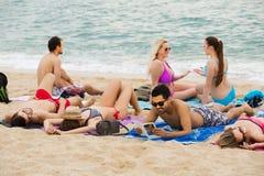 Adultos que se relajan en la playa arenosa Foto de archivo