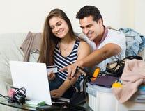 Adultos que se sientan cerca del ordenador portátil y del equipaje Foto de archivo libre de regalías