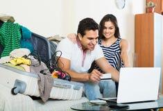 Adultos que se sientan cerca del ordenador portátil y del equipaje Fotografía de archivo