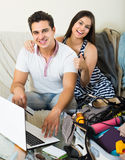Adultos que se sientan cerca del ordenador portátil y del equipaje Fotos de archivo