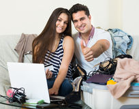 Adultos que se sientan cerca del ordenador portátil y del equipaje Foto de archivo