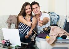 Adultos que se sientan cerca del ordenador portátil y del equipaje Imagen de archivo libre de regalías