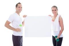 Adultos que sostienen una cartulina en estudio Imagenes de archivo