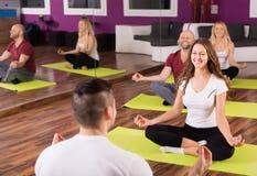 Adultos que tienen clase de la yoga Imágenes de archivo libres de regalías