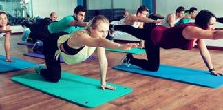 Adultos que tienen clase de la yoga en club de deporte Foto de archivo libre de regalías