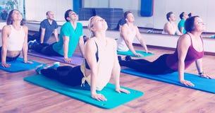 Adultos que tienen clase de la yoga en club de deporte Imagenes de archivo