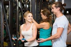 Adultos que tienen entrenamiento de la fuerza bajo control del coche en gimnasio Imagen de archivo