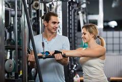 Adultos que tienen entrenamiento de la fuerza bajo control del coche en gimnasio Fotos de archivo libres de regalías