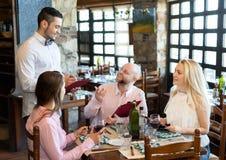 Adultos que tienen la cena y el camarero Imágenes de archivo libres de regalías