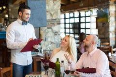 Adultos que tienen la cena y el camarero Imagen de archivo libre de regalías