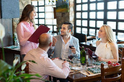 Adultos que tienen la cena y el camarero Imagen de archivo