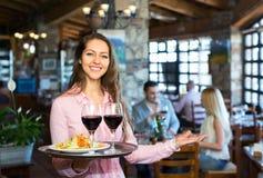 Adultos que tienen la cena y el camarero Fotos de archivo