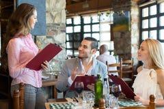 Adultos que tienen la cena y el camarero Foto de archivo