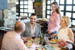 Adultos que tienen la cena y el camarero Fotografía de archivo