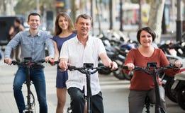 Adultos que viajan a través de ciudad en bicicletas Fotografía de archivo