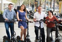 Adultos que viajan a través de ciudad en bicicletas Imágenes de archivo libres de regalías