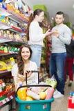 Adultos sonrientes que eligen la comida enlatada Imágenes de archivo libres de regalías