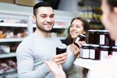 Adultos sonrientes que eligen la comida enlatada Fotografía de archivo