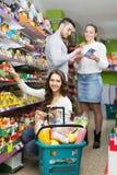 Adultos sonrientes que eligen la comida enlatada Imagenes de archivo