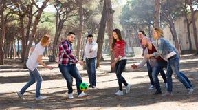 Adultos sonrientes que persiguen la bola al aire libre Fotografía de archivo libre de regalías