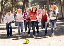 Adultos sonrientes que persiguen la bola al aire libre Imagen de archivo