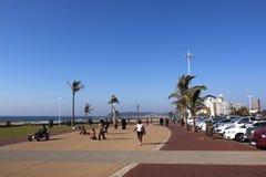 Adultos y niños en la 'promenade' frente al mar pavimentada Imagenes de archivo
