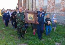 Adultos y niños que participan en la procesión con el icono Imagenes de archivo
