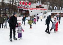 Adultos y niños que patinan en parque Fotos de archivo libres de regalías