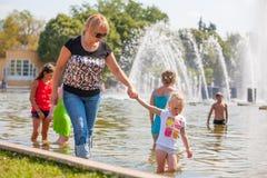 Adultos y niños que se colocan en agua Imagen de archivo libre de regalías