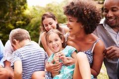 Adultos y niños que se sientan en la hierba en un jardín Imágenes de archivo libres de regalías