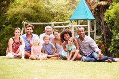 Adultos y niños que se sientan en la hierba en un jardín, retrato del grupo Imagenes de archivo