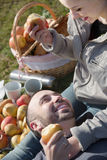 Adults with apples in nature. Portrait of young positive adults with apples and sandwitches in nature Royalty Free Stock Images