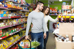 Adults buying canned food in shop Stock Images