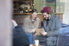Adults in a cafe using a digital tablet Stock Photography