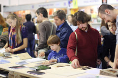Adults and a child read the books at the book fair Stock Photos