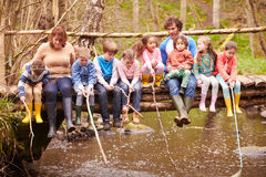 Adults With Children On Bridge At Outdoor Activity Centre Stock Photo