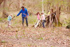 Adults And Children Building Camp At Outdoor Activity Centre Stock Photo