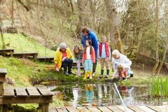 Adults And Children Exploring Pond At Activity Centre Stock Photography