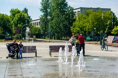 Adults and children by fountain. royalty free stock photography
