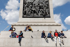 Adults and children rest at the base of the Nelson column Royalty Free Stock Image