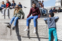 Adults and children rest at the base of the Nelson column Royalty Free Stock Photos
