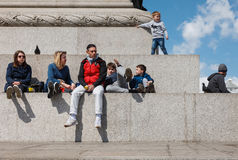 Adults and children rest at the base of the Nelson column Stock Image