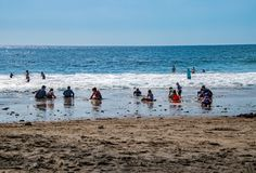 Adults and children sitting in the mud and sand by the ocean stock photography