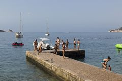 Adults and children swim and rest on the pier of the city beach Stock Images