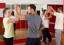 Adults dancing in dance studio. Smiling adults dancing bachata together at dance studio royalty free stock photo